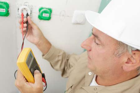 a man measures the voltage