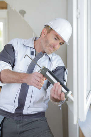 construction worker installing window in house Stock Photo