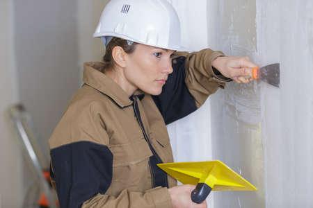 vrouwelijke stukadoor bezig met binnenmuur