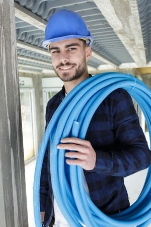 technician holding water pipes indoors