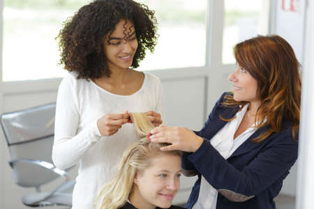 a hairdressing apprentice doing hairstyle Stock Photo