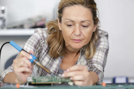 woman soldering elements of circuit board Standard-Bild