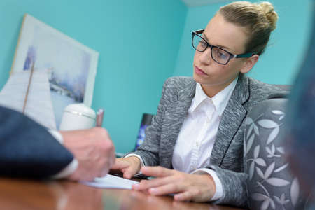 funeral director watching client sign contract Stock Photo