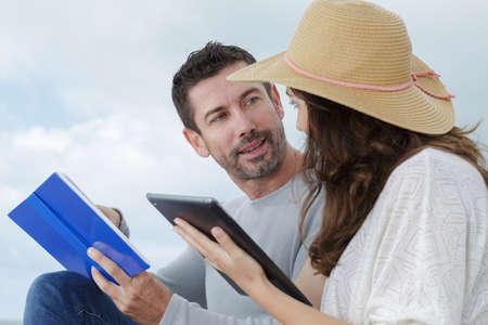 couple in discussion man holding book woman holding tablet