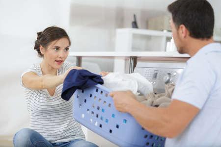couple having an argument about laundry basket