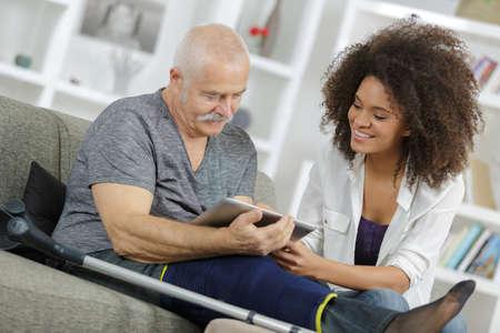 homme blessé regardant une tablette numérique avec une jeune femme Banque d'images