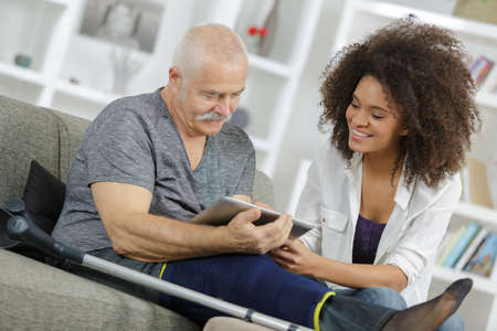 injured man looking at digital tablet with young lady