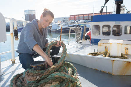 woman pulling rope on deck of a boat