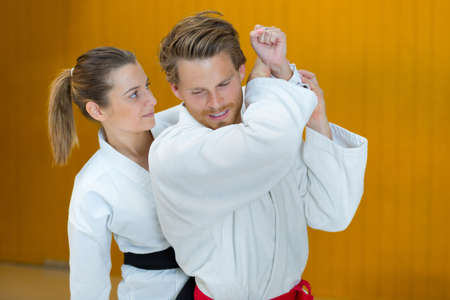 man and woman fighting at aikido training