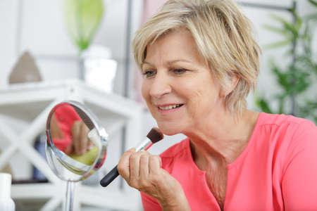 mujer mayor, delante de, espejo, poner maquillaje