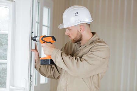 male contractor using drill on window