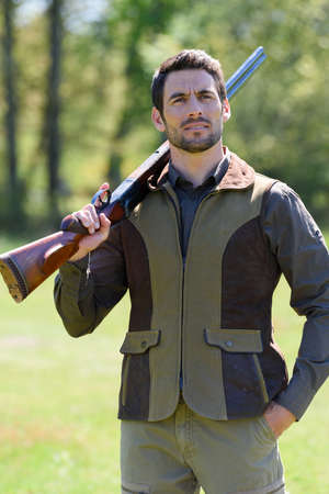 male farmer carrying a rifle walks along