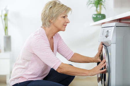 elderly woman next to a washing machine Stockfoto
