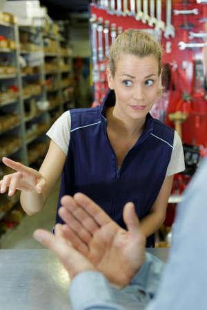 trabajadora del taller que señala la dirección al cliente
