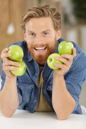 handsome man holding a apples Фото со стока