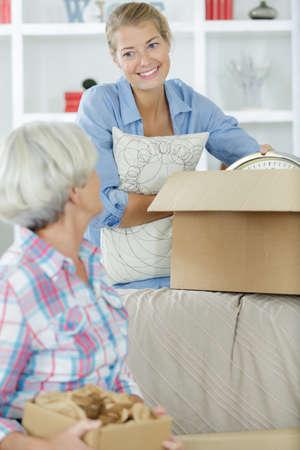 Frau hält Karton und hilft Mama beim Auspacken