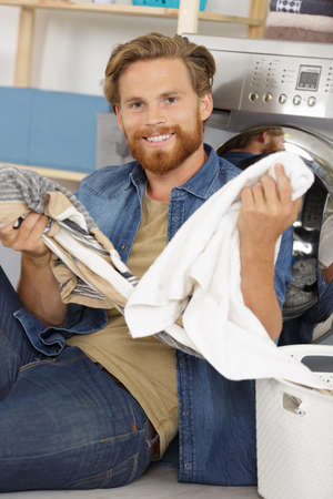 man with a laundry basket next to a washing machine Stockfoto