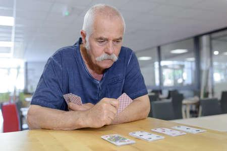 senior man playing cards alone