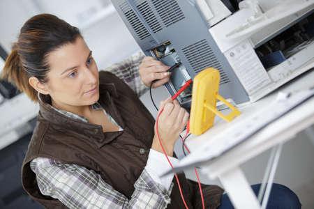 Technician using multimeter on appliance Stok Fotoğraf