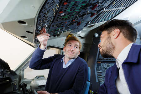 engineer talking to trainee in cockpit of aircraft