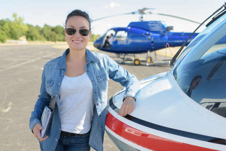 pretty pilot woman next to helicopter
