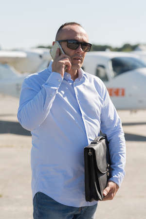 businessman standing on landing strip near private jet