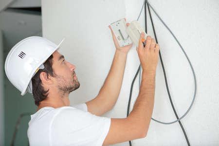 a young man repairing socket