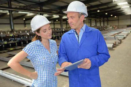 Two workers talking in industrial unit