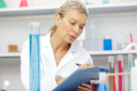 mature female lab assistant doing scientific experiments in laboratory Foto de archivo