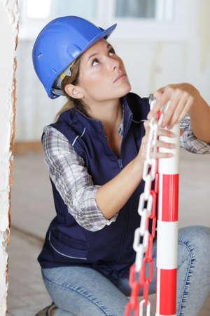 travailleur mettant en place une chaîne d'exclusion sur chantier Banque d'images
