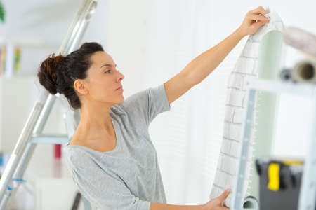 portrait of woman putting up wallpaper