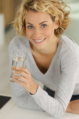 satisfied young woman drinking water