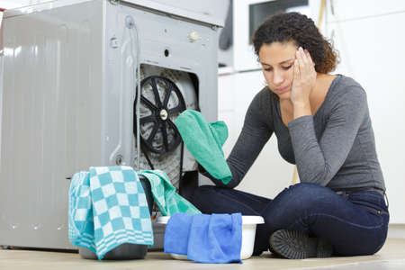 woman worried about her washing machine Stock Photo