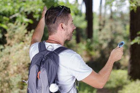 rear view of male backpacker holding compass