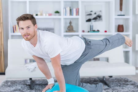 young man in lounge room doing exercise Banco de Imagens