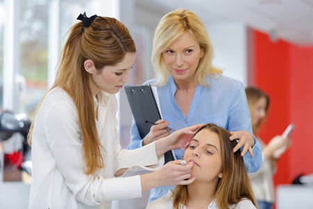 trainee beautician applying cosmetics supervision in salon