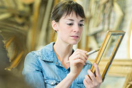 woman restoring an antique frame