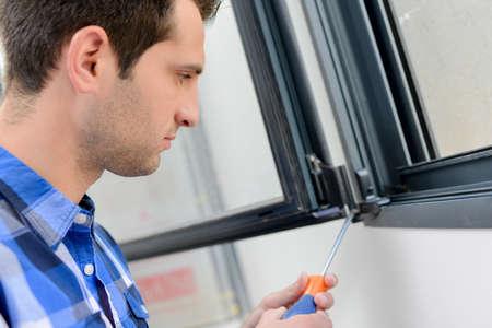 male worker is fixing window