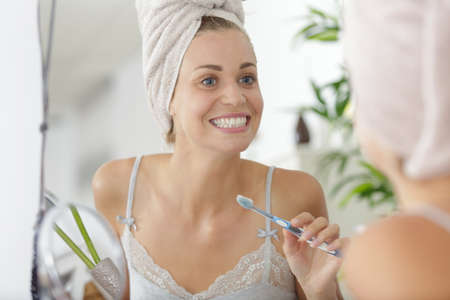 portrait of beautiful young woman brushing teeth 免版税图像