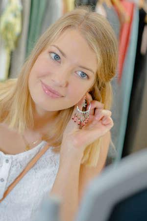 Girl holding earring to her ear Imagens
