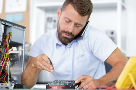 male worker calling customer while disassembling a pc Stock Photo