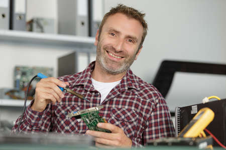 man holding soldering iron and computer motherboard
