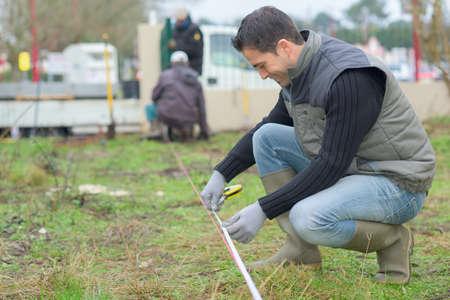 surveyor worker making measurement in the garden