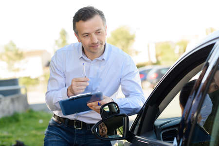 portrait of driving instructor outside car
