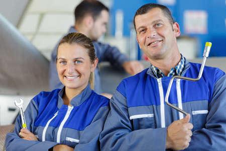 man and woman auto mechanics looking at camera