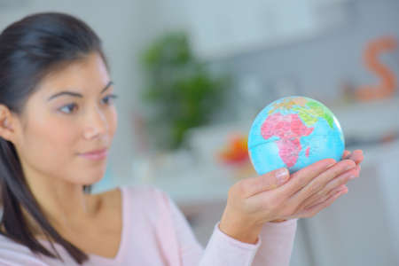 woman holding a globe on her hands