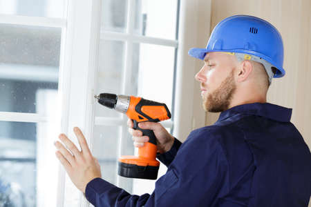 male builder using a drill