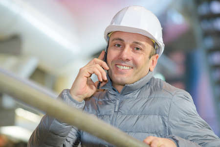 smiley engineer holding smart phone