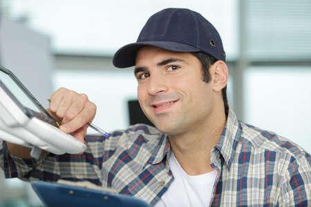 happy repairman repairing broken printer fax machine Stock Photo
