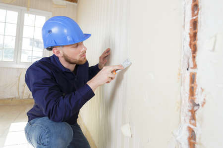 male plasterer in uniform polishing the wall Standard-Bild